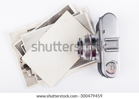 Old camera and stack of photos - stock photo