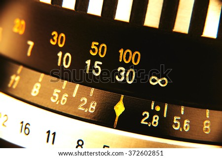 Old camera lens in vintage style. Numbers of distance and aperture. Knobs made of steel. - stock photo