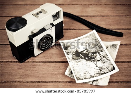 Old camera with a couple of old photos of a young soldier on a table. The image has a vintage effect. - stock photo