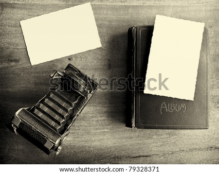 Old camera with album and two empty pictures - stock photo