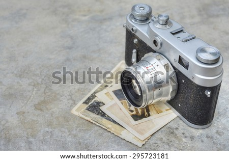 Old camera with photographs on a gray concrete background with copy space - stock photo