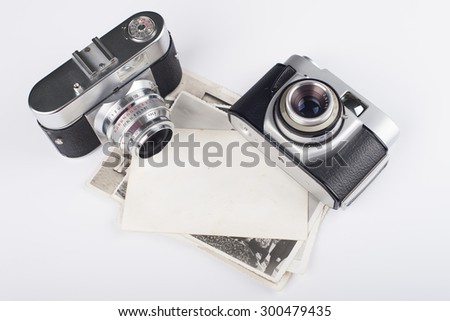 Old cameras and stack of photos - stock photo