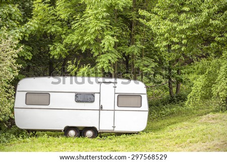 Old camping trailer standing in woods on summer day, nature holiday concept.