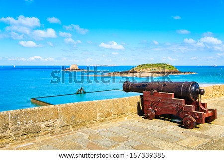 Old cannon along  Saint Malo wall ramparts and fort on background. View to Dinard. Brittany, France, Europe