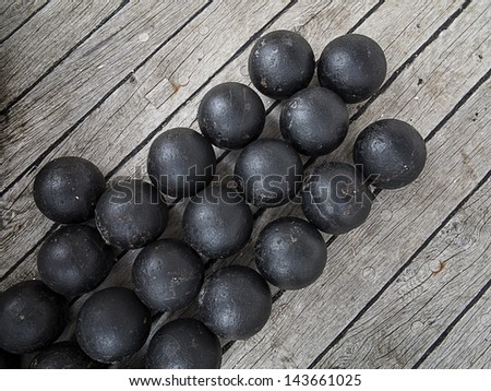 Old cannon balls placed on deck of and old Danish frigate. - stock photo