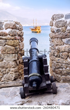 Old cannon menacing a ship from the coastal fort. Seljuk dockyard in Alanya, Turkey. - stock photo