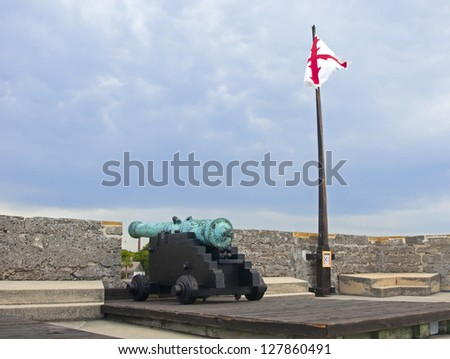 Old canon aiming at the sea on an overcast day, Castillo de San Marcos, St. Augustine, Florida, 16th century. - stock photo