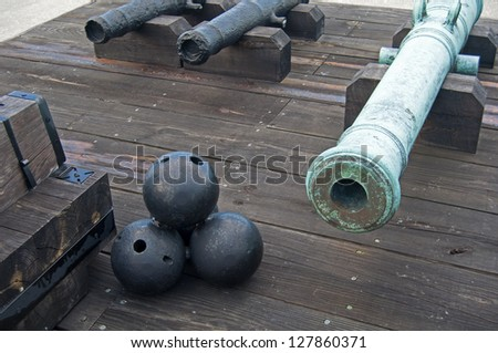 Old canons and cannonballs in a fort, on an overcast day. Old Castillo de San Marcos, St. Augustine, Florida - stock photo