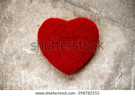 Old canvas background with a small red heart - stock photo