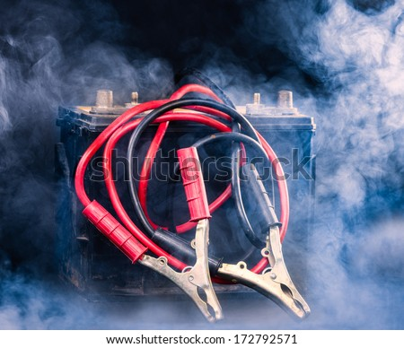 Old car battery and the jumper cables, smoky environment - stock photo
