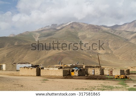Old car body rusting in the Pamir mountains, Tajikistan, Central Asia - stock photo
