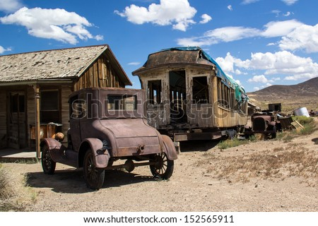 Old car, building and abandoned railcar in Goldfield, Nevada - stock photo