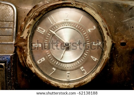 Old car dashboard clock pointing ten to seven