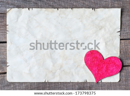 Old card on aged wood decorated with wooden heart  - stock photo