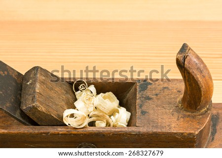 Old carpenter plane and wood shavings on a wooden table - stock photo