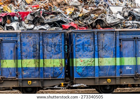 old cars were scrapped in a trash compactor. scrapping premium for car wrecks. scrap is loaded onto the train - stock photo