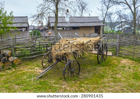 Old cart stands at the village courtyard - stock photo