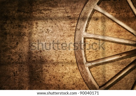 Old cart wheel against wall