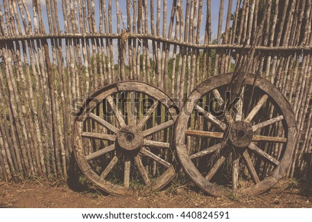 Old cart wheel as a symbol of fortune and fate. Two old waggon wheels near the wooden fence, filtered with soft pastel colors with filters. - stock photo