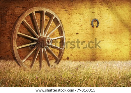 Old cartwheel in barn - stock photo
