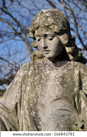 Old carved stone angel in Hammersmith Margravine cemetery, London, UK
