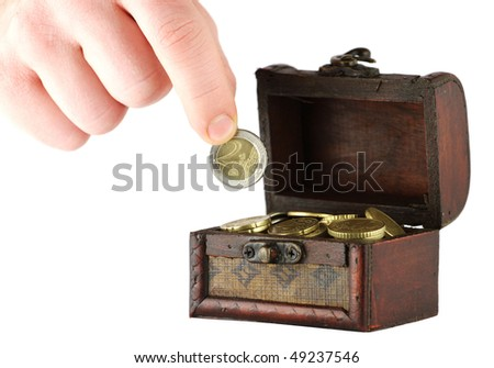 Old casket full of coins and a hand holding two euros coin - stock photo