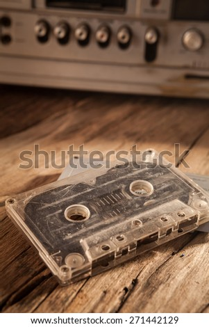 Old cassette tapes and cassette player on wooden surface - stock photo
