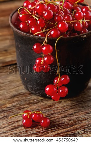 Old cast iron black cup full of fresh ripe red currant on a  wooden table. - stock photo