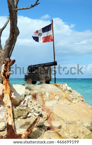 old cast-iron cannon, and the ship anchor in front of of the flag of the Dominican Republic on the Atlantic coast