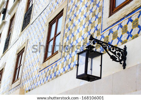 Old cast iron lamp on the tiled wall in Lisbon, Portugal  - stock photo