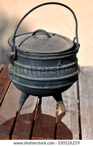Old cast-iron pot for cooking, isolation against a white background - stock photo