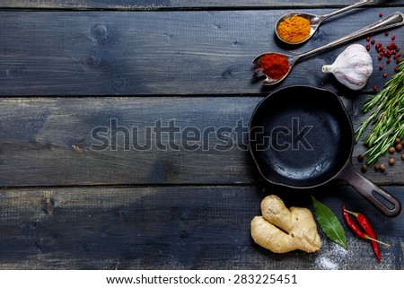 Old cast iron skillet and ingredients on rustic wooden background. Vegetarian food, health or cooking concept. - stock photo
