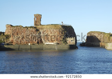 old castle and harbour entrance at Dunbar, East Lothian, Scotland in winter sunlight - stock photo