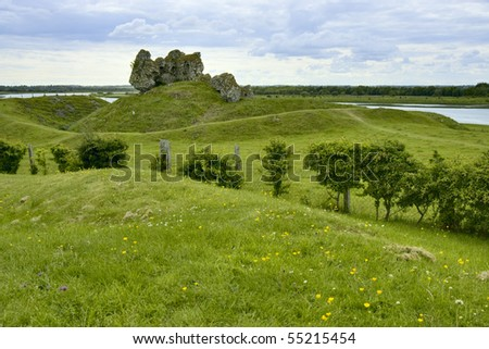 Old Castle in Republic of Ireland against grassy hills and cloud filled sky - stock photo