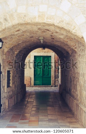 Old castle interior and a green door in the end - stock photo