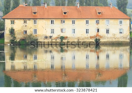 Old castle on river with swans and ducks, reflection in water - stock photo