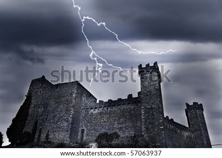old castle with dark ominous clouds and lightning - stock photo