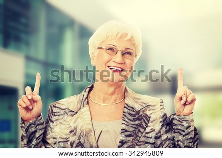 Old casual lady pointing up on copy space - stock photo