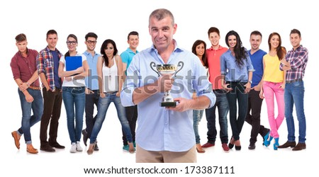 old casual man holding a trophy cup in front of his winning young team of people on white background