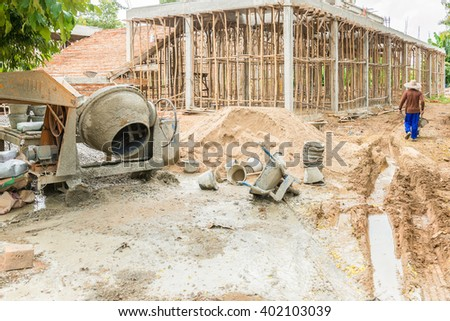 Old Cement mixer machine with sand truck stop beside at a construction site. - stock photo