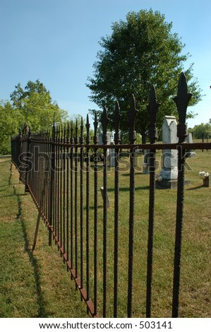 Old Cemetery - A rusty railing surrounds an old graveyard in the country in Kentucky, USA.  Because people are just dying to get in!  (Old joke, sorry, just had to say that!) - stock photo