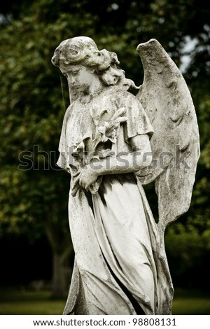 Old cemetery angel sculpture made of stone - stock photo