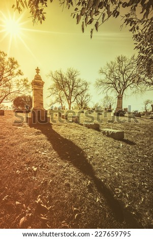 Old cemetery - vintage look with sun light - stock photo