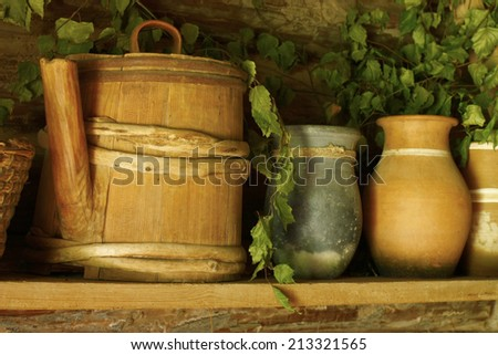 Old ceramic and wooden utensils on the shelf - stock photo