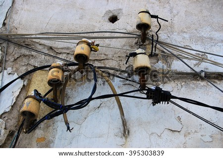 Old Ceramic insulators on the wall. Connection wiring. - stock photo