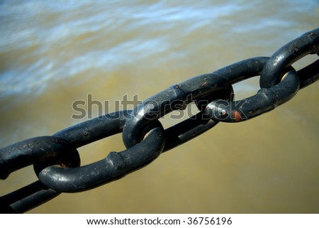 Old chain over water - stock photo