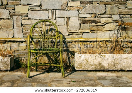 Old chair against a stone wall. Lonely old chair - stock photo