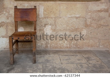 old chair near the old wall - stock photo