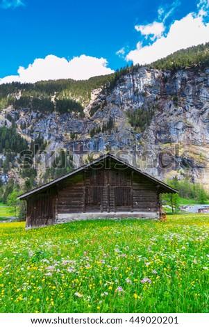 Old chalet on green mountain slope. Swiss Alps. Lauterbrunnen, Switzerland, Europe - stock photo