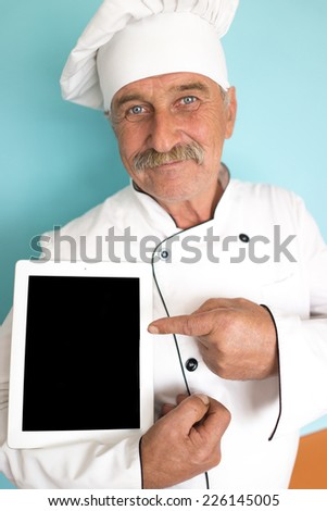 Old chef in white cook uniform pointing on tablet display